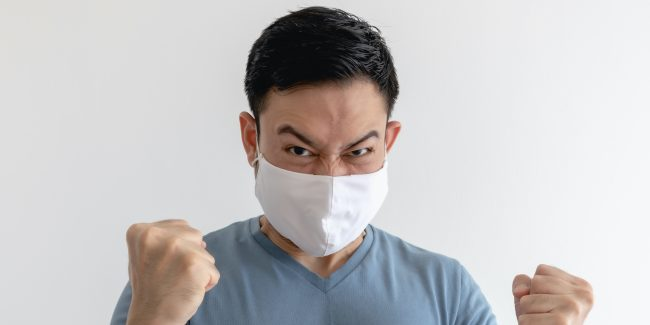 Angry man with mask on with fists up